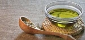 hempseed oil in a glass bowl, wooden spoon with seeds, back ground timber top