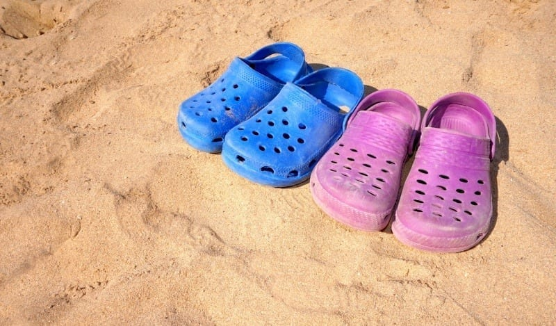 boys and girls pink and blue plastic crocs on sunny beach