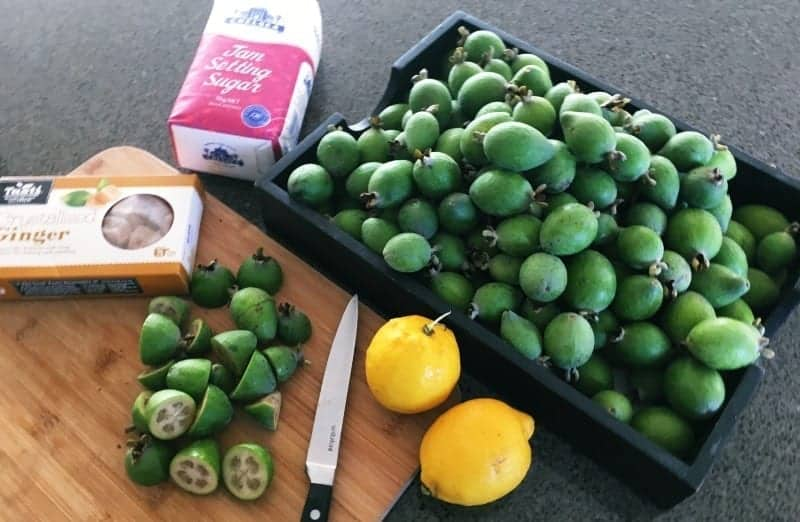 Feijoa, ginger, lemon, bag of sugar on a timber chopping board