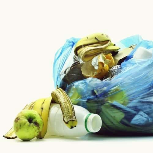 picture of rubbish bag with fruit peel and empty carton falling out