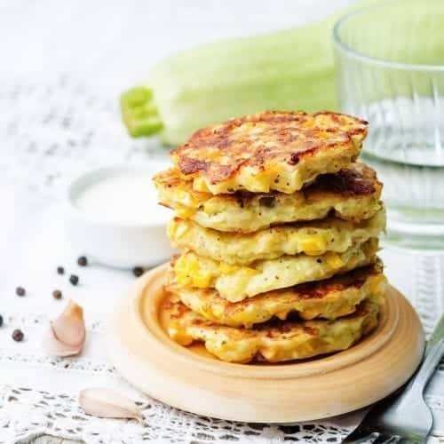 stack of fritters with corn, on a plate, garlic, laid on a table