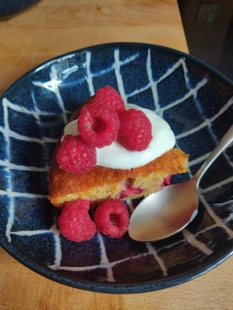 Raspberry Pud with fresh raspberries and cream on a blue ceramic bowl