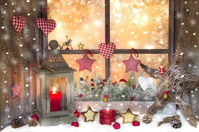 Red Christmas decoration with lantern on window sill and snow and lights
