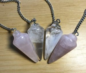 4 clear quartz pendulums on a wooden background