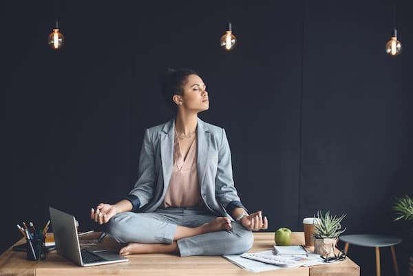 lady sitting on a busy office desk doing a mantra for alleviating stress