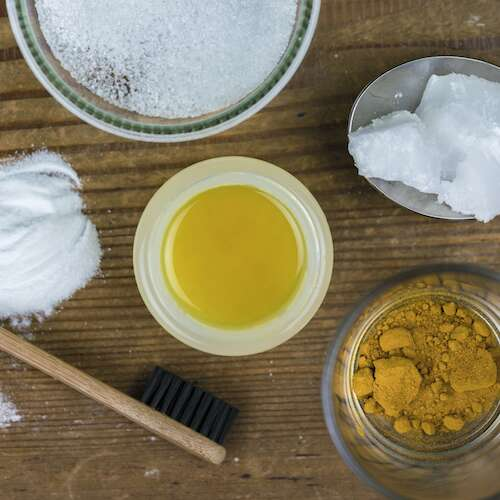 DIY toothpaste with ingredients, coconut oil, turmeric, baking soda, and bamboo toothbrush