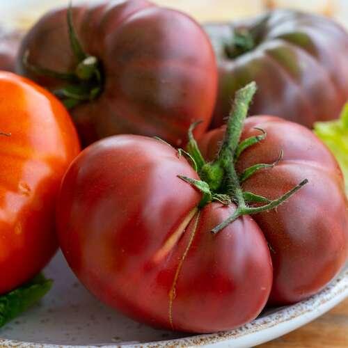 big raddish-purple heirloom tomatoes Black Krim on plate